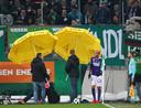Holzhauser beschermd door paraplu's.