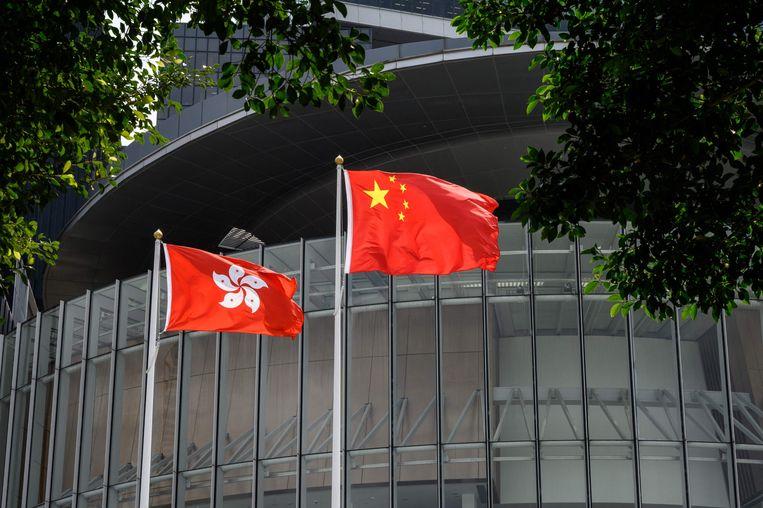 De vlaggen van Hongkong en China wapperen buiten het gebouw van het parlement van de stad.  Beeld AFP