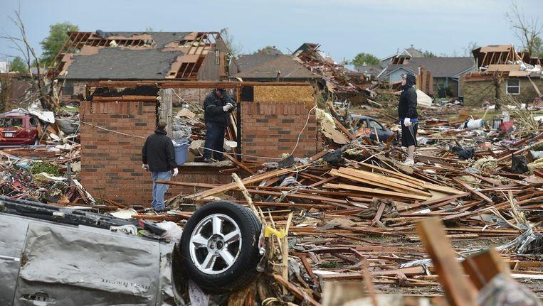 Inwoners van Moore, Oklahoma, kijken of er nog spullen te redden zijn uit de puinhopen die de tornado van hun huis heeft gemaakt. Beeld epa