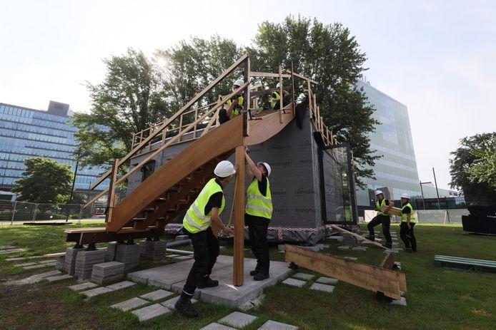 Studenten van de universiteit bouwen op de campus aan een duurzaam houten huis.