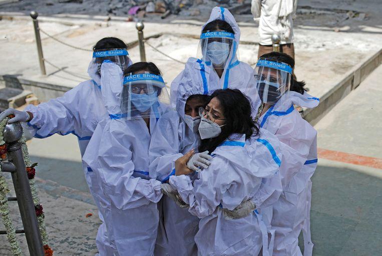 Indiërs dragen beschermende kledij bij een crematorium in Delhi. Beeld REUTERS