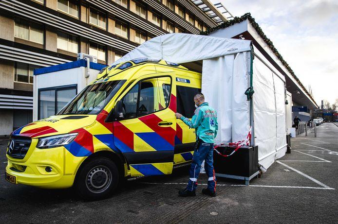 Een ambulance bij een portakabin bij de spoedeisende hulp van het Groene Hart Ziekenhuis in Gouda, waarin patiënten waarvan vermoed wordt dat ze besmet zijn, worden opgevangen. Zo kunnen de stromen patiënten met en zonder corona worden gescheiden. (archieffoto)