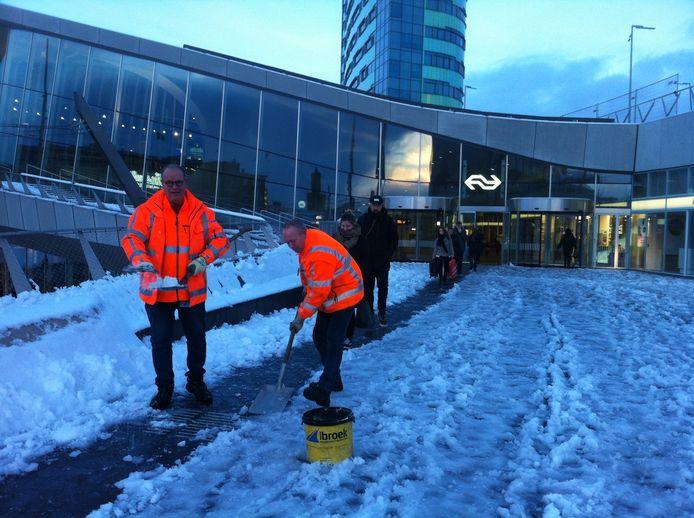 Gemeentemedewerkers maken het looppad naar de ingang van Arnhem Centraal sneeuwvrij.