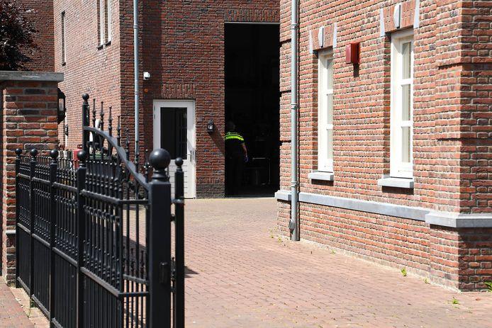 Een politieagent in de woning van de van witwassen verdachte Ossenaar.