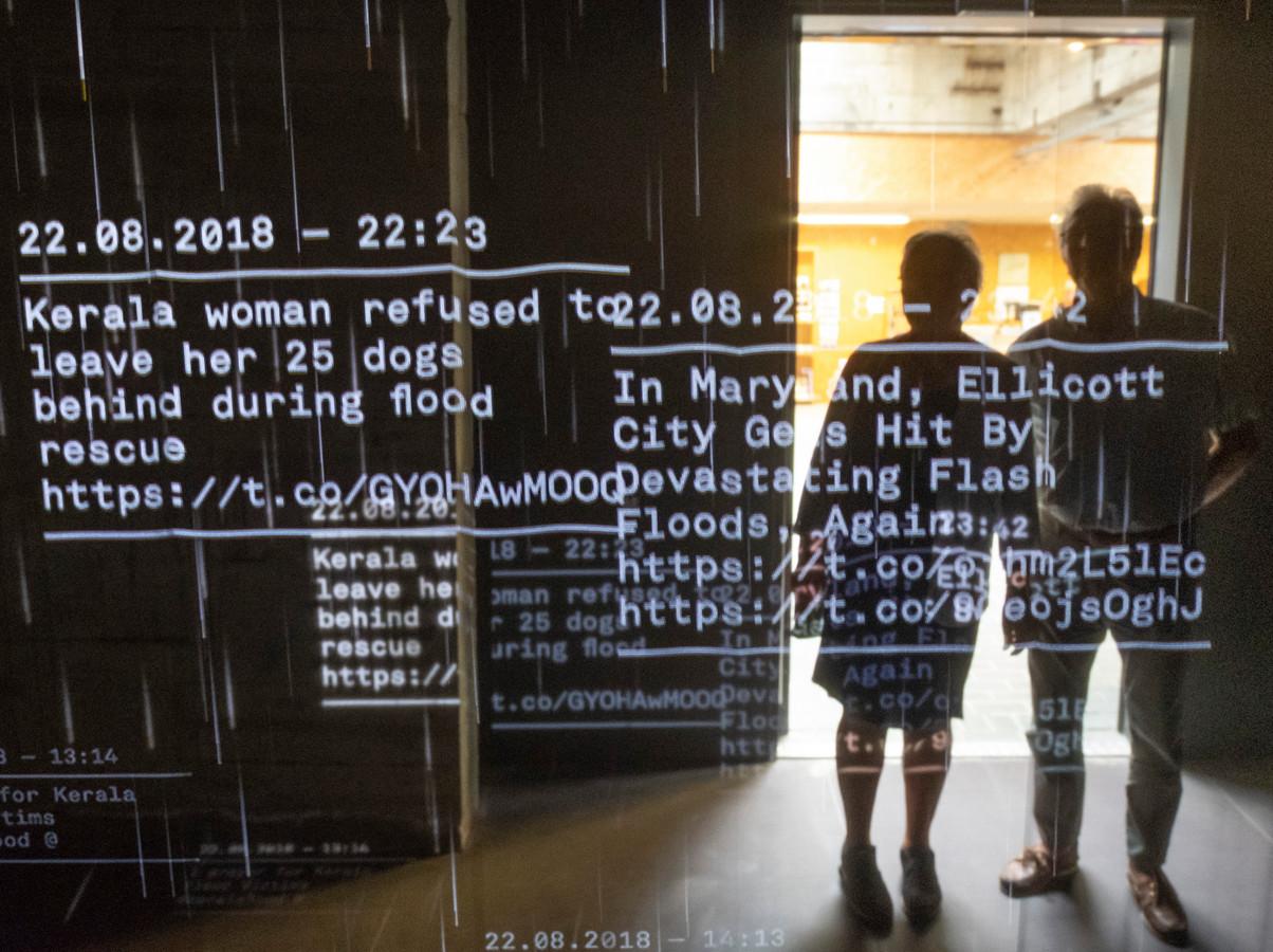 Jan en Riet Moret uit Gouda bekijken de regen aan tweets op de doeken in het Watersnoodmuseum in Ouwerkerk.