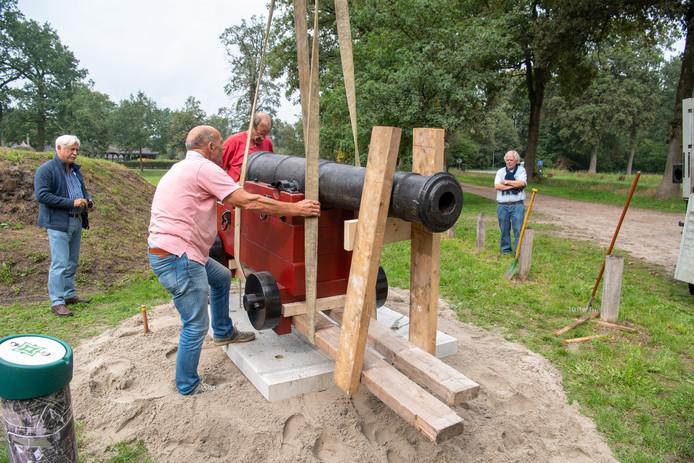 Jan Mulder (links) en Willem Bemboom (rechts) kijken toe terwijl Wim Herbrink (m) het kanon op de vestingwal helpt plaatsen.