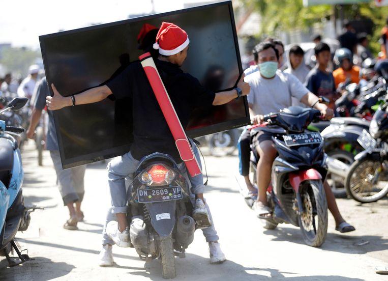Plunderaars in Palu gaan er vandoor met een breedbeeld televisie. De lokale overheid grijpt op last van de centrale overheid niet in, zo meldt AFP.  Beeld EPA