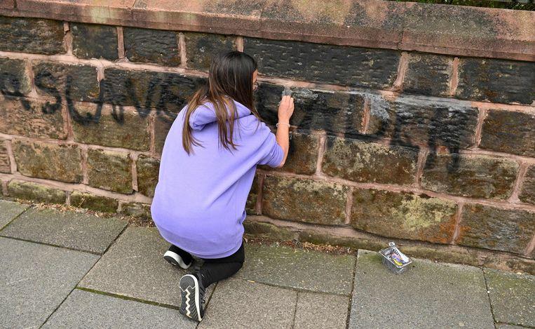 Een bewoner probeert graffiti van de muur te verwijderen.  Beeld AFP