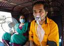 Een coronapatiënt met een zuurstofmasker wacht tot hij behandeld kan worden in het ziekenhuis van Ahmedabad, India.