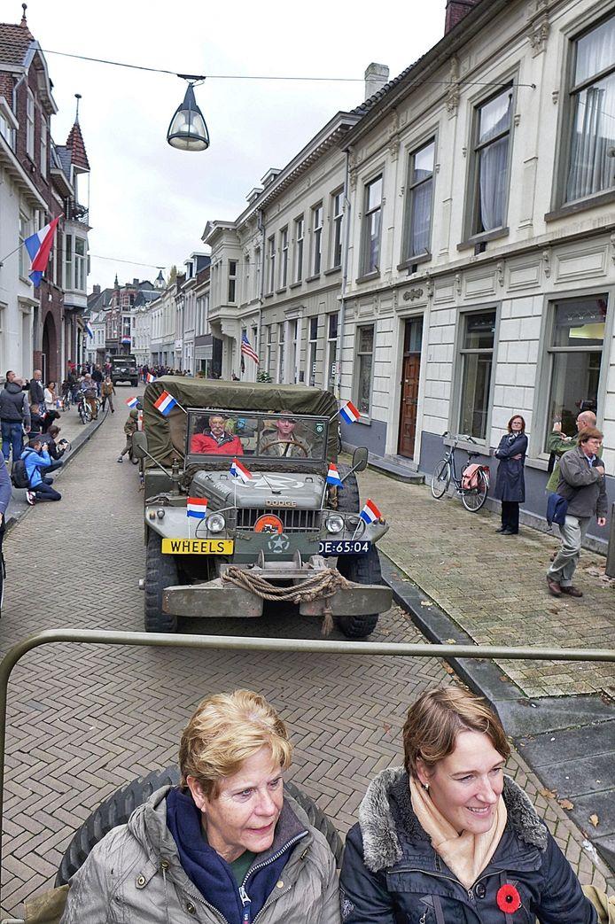 Lenie Markerink (links) en Lieske Jorritsma rijden op de achterbank van een Bantam jeep mee in de straatparade in Tilburg.