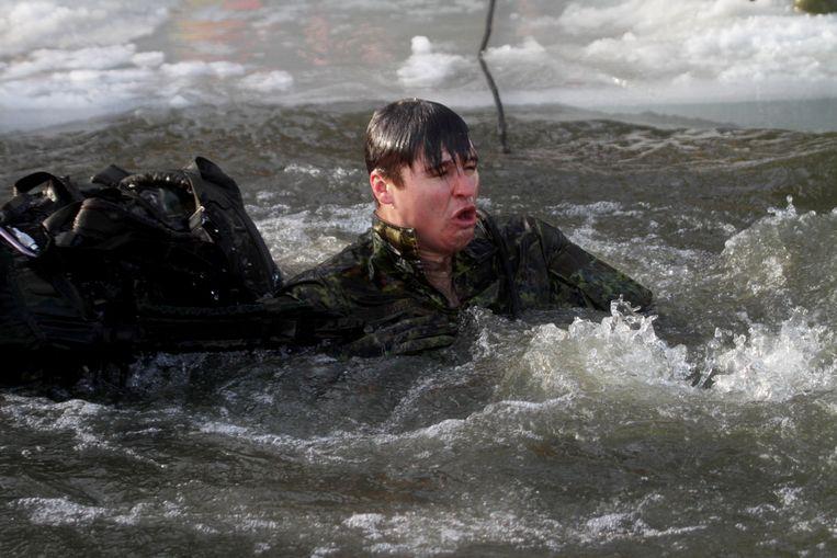 Een Navo-militair oefent in Letland met soldaten uit Albanië, Polen, Italië, Canada, Spanje, Slovenië en Letland. Beeld EPA