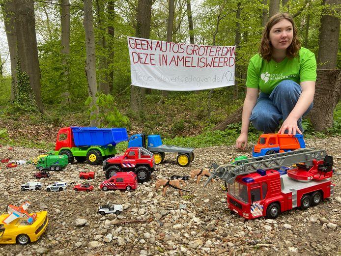 Nina Saelmans van de Jonge Democraten zet de speelgoedauto's neer op het bospad in Amelisweerd.