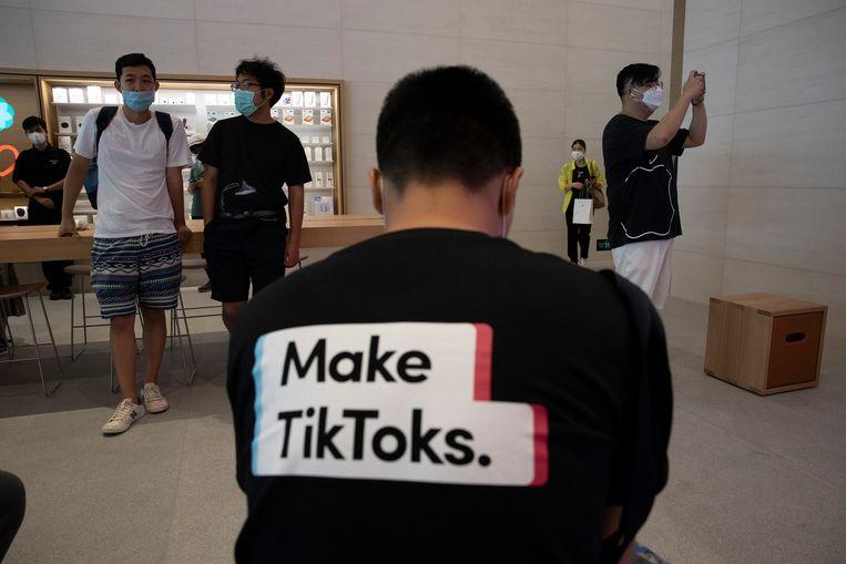 Een man met een t-shirt van TikTok in een Applewinkel. Beeld AP