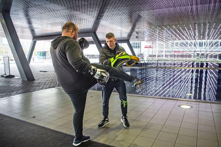 Onder een overdekt deel van de Rai in Amsterdam wordt kickboksles gegeven. Vanaf volgende week zou dit weer in een sportschool mogen. Beeld Guus Dubbelman / de Volkskrant