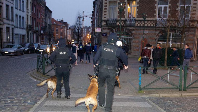 Politieagenten met speurhonden aan de veiligheidsperimeter rond de Karperstraat in molenbeek, gisteravond. Beeld BELGA