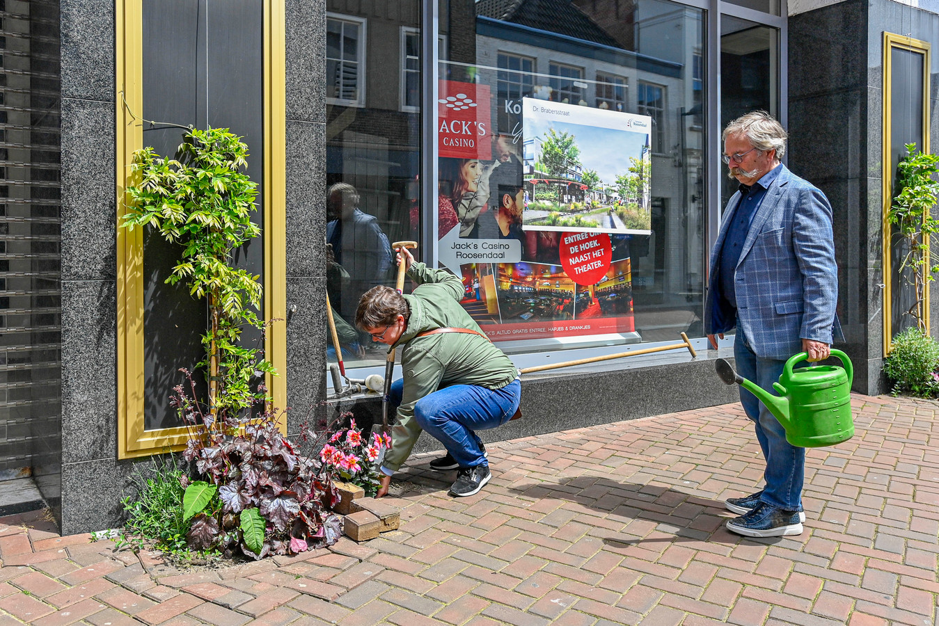 De Raadhuisstraat in Roosendaal is vergroend met geveltuintjes. Wethouder Inge Raaijmakers plant, wethouder Cees Lok staat klaar met de gieter.