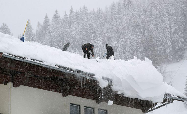 Mannen verwijderen de sneeuw van het dak in Filzmoos. Beeld REUTERS