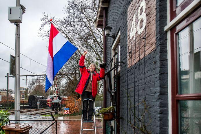 Aline Barnhoorn hangt de vlag uit omdat ze  haar spoorweghuisje niet terug hoeft te brengen naar de originele staat.