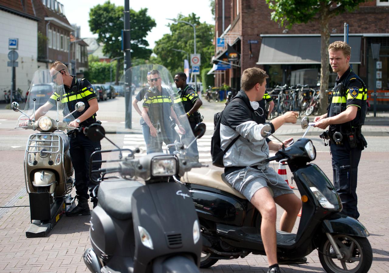 Agenten voeren een scootercontrole uit. De bestuurder is niet de persoon uit dit verhaal.
