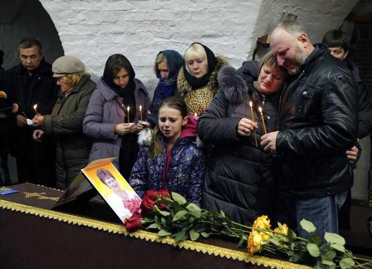 Nabestaanden van slachtoffers van de crash met de Russische airbus tijdens een begrafenis. Beeld EPA