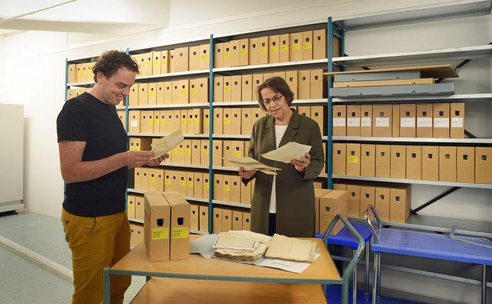 Relatiebeheerder cultuurhistorie Ilja Mostert en gemeentearchivaris Ineke van den Broek van het gemeentearchief Schouwen-Duiveland met een deel van het Weeskamerarchief.