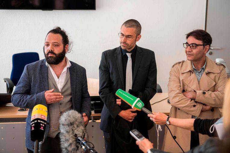 Advocaat Patrick Kroker (C) en mede-aanklagers Wassim Mukdad (L) en Hussein Ghrer (R) beantwoorden vragen van journalisten buiten de rechtszaal tijdens een pauze in een proces tegen twee Syrische beklaagden die worden beschuldigd van door de staat gesponsorde marteling in Syrië, afgelopen 23 april , 2020 in Koblenz, West-Duitsland. Beeld AFP