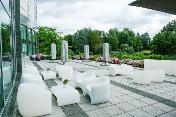 Op het terras achter het hotel staan de tafels en stoelen wat verder uit mekaar.