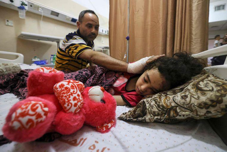 De Palestijne Ryad Eshkuntana zit bij het bed van zijn gewonde dochter.  Beeld AFP