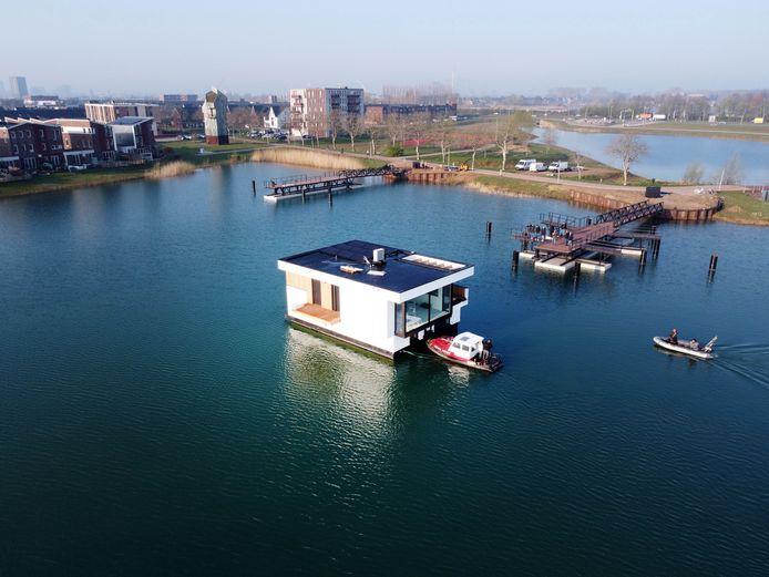 De eerste drijvende villa op weg naar zijn definitieve plek. Op de achtergrond het vasteland van Lent.
