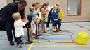 Wethouder Kees Grootswagers pompt samen met de jongste sporters de ballon op om de sporthal te openen.