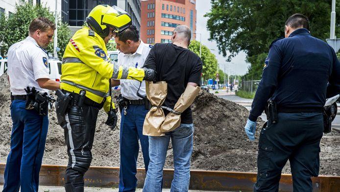 Politieagenten arresteren Ton de H. na de moord op zijn collega Marjon van der Kraan.