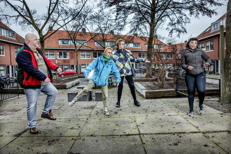 Deelnemers van 'Gezond Noord' doen een warming-up voor hun wandeling in het Noorderpark. Vlnr: Gerrit Klarenbeek (64) , Els Annegarn, Simone van Dijk (64) en Graciella van der Kust (44). Beeld Jean-Pierre Jans