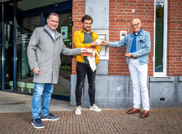 Tim van Melis krijgt een chocolade Gemertse gulden met daarop de door hem ontworpen afbeelding, van chocolatier Wilco Dijsselbloem (links) en VVV-voorzitter Bert Mickers. Ze staan voor de plaquette over de laatste gulden in het gebouw van de Rabobank.