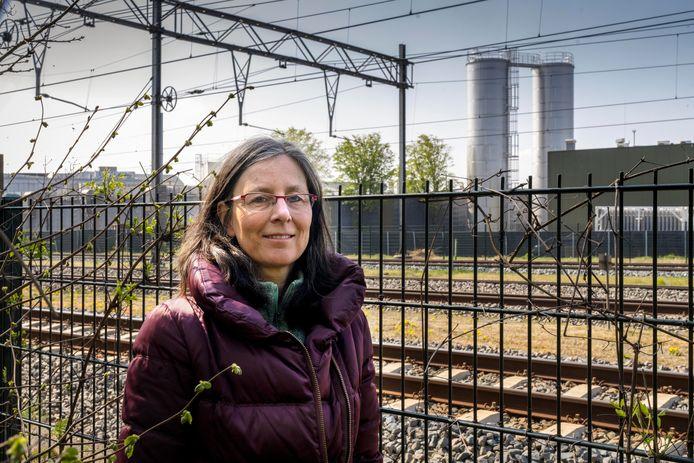 Mirjam Bemelmans met aan de andere kant van het spoor de twee illegaal geplaatste watertanks van Vion.
