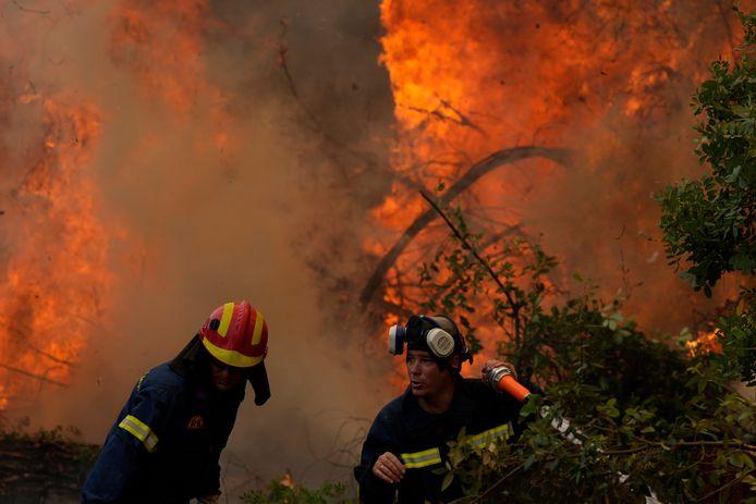 Les pompiers opèrent dans le village d'Ellinika sur l'île d'Evia, à environ 176 kilomètres (110 miles) au nord d'Athènes, en Grèce, lundi 9 août 2021.
