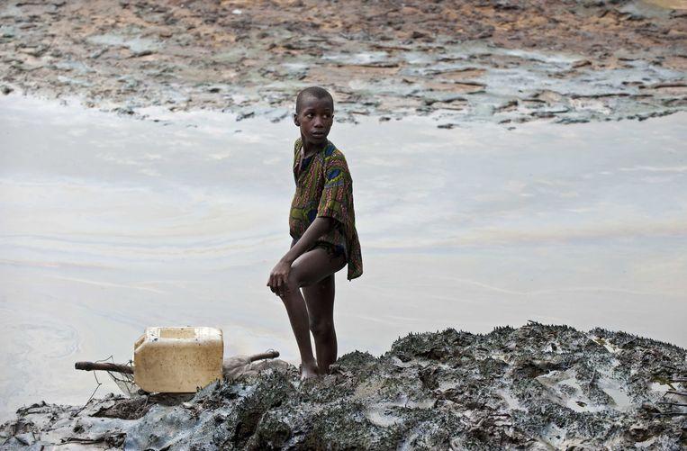 Een jongen staat op de zwaar vervuilde oever van een rivier bij Goi, NIgeria. Beeld EPA
