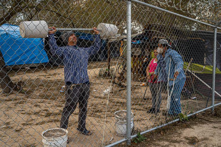 Een asielzoeker doet zijn workout met zelfgemaakte dumbbells in het vluchtelingenkamp in Matamoros, aan de Mexicaans-Amerikaanse grens. De Guatemalteekse Francisco Caal en Jeanet Trujillo kijken toe. Beeld Alejandro Cegarra