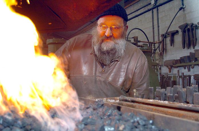 Kunstsmid Juul Baltussen bij het smidsvuur in zijn werkplaats in Westerbeek.