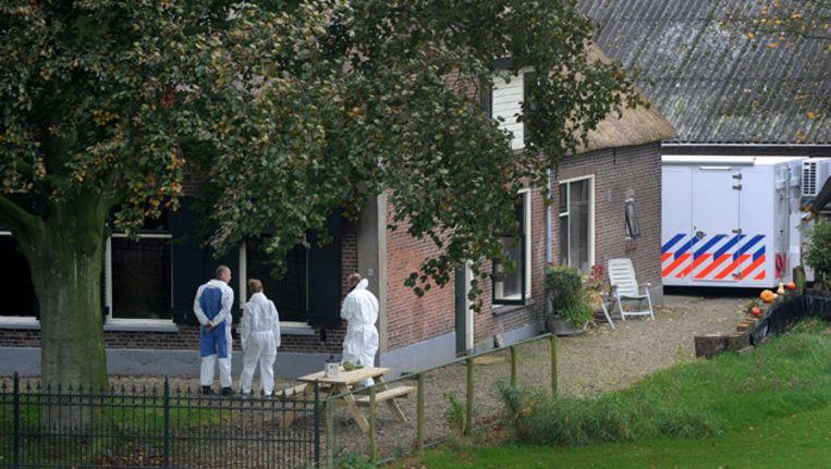 Rechercheurs onderzoeken het terrein rond de boerderij waar na een brand de lichamen van vier gezinsleden zijn gevonden Beeld anp