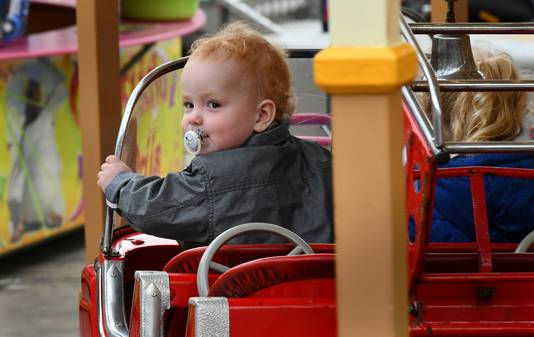 Het jongetje geniet in de brandweerauto in de draaimolen op de stille kermis van Houten.