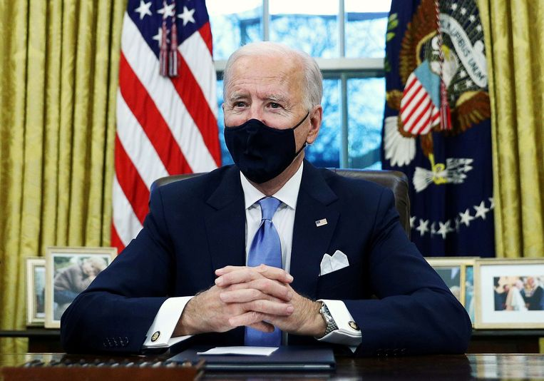 Amerikaans president Joe Biden in zijn nieuwe werkplek, het Oval Office in het Witte Huis. Beeld REUTERS