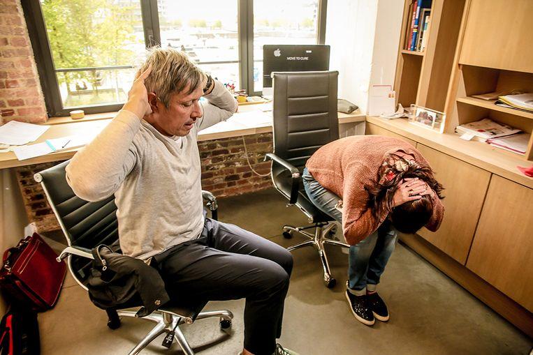 Oefening aan je bureau: Vouw je handen achter je hoofd, zet je voeten plat op de grond, buig je hoofd en probeer met je neus je knieën te raken. Beeld Pieter-Jan Vanstockstraeten / Photonews