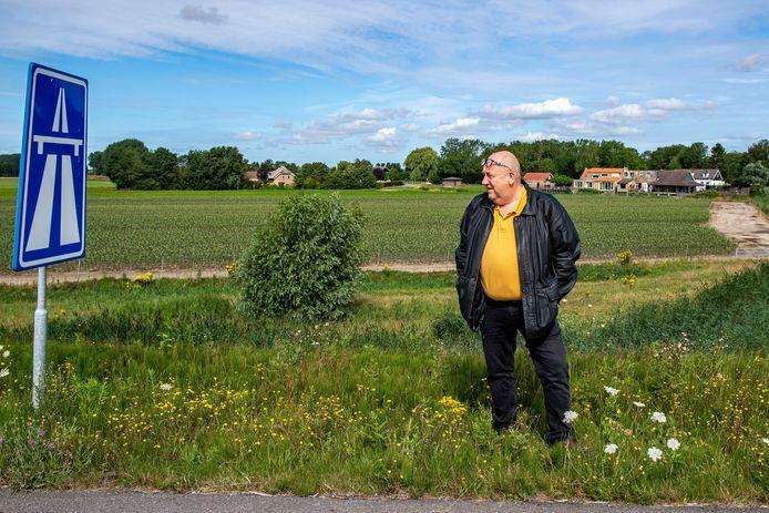 Paul van Nieuwenhuyzen bij snelwegbord van de A4 bij Steenbergen. Hij woonde er ooit vlak naast (rechts achter) en moest verhuizen.
