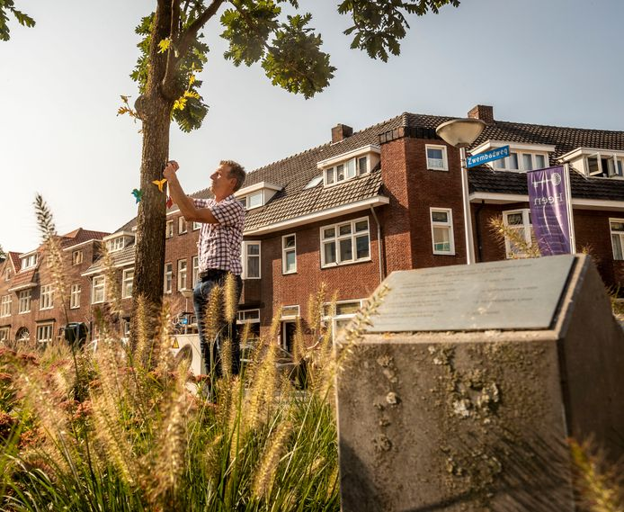 Arjen van Halem hangt vredesduiven op bij de vier herdenkingsbomen. Op de voorgrond de plaquette ter herinnering aan de vier verdwenen Wit-Russische mannen.