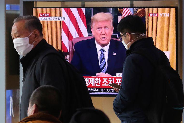 Ook in Zuid Korea werd de speech van president Donald Trump over de aanpak van het coronavirus live uitgezonden. Koreanen lopen met mondkapjes op langs het tv-scherm.   Beeld AP Photo/Ahn Young-joon