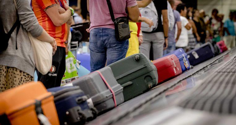 Reizigers wachten op hun koffers bij de bagageband. Foto ter illustratie.