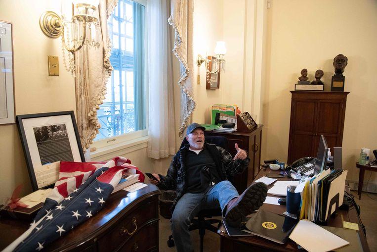 Woensdag 6 januari in het Capitool: een indringer poseert triomfantelijk in Pelosi's werkkamer. Beeld AFP