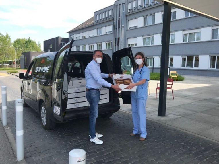 Een medewerker van het Waregems ziekenhuis neemt de gebakjes in ontvangst.
