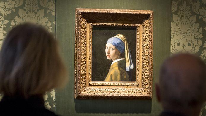 Bezoekers in het Mauritshuis kijken naar het beroemde schilderij het Meisje met de Parel van Johannes Vermeer.