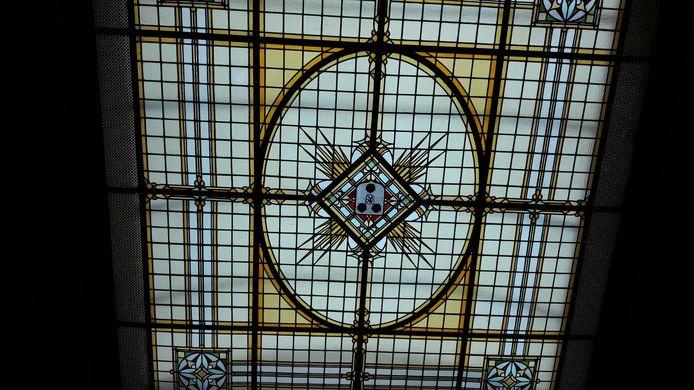 Een van de grote glas-in-loodpanelen die aan het plafond hangt: het wapen van Roosendaal.